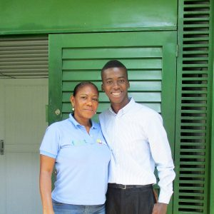 Eduardo, a successful graduate standing outside the building of partner charity Fedut