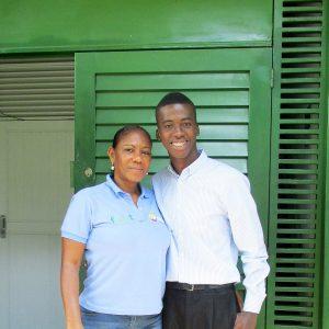 Eduardo, a successful graduate standing outside the building of partner charity Fedut